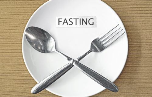 32697671 – fasting paper and fork with spoon symbol on white plate